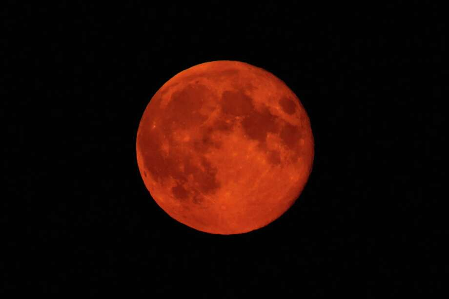 HIGH WYCOMBE, ENGLAND - SEPTEMBER 09:  A blood red Supermoon is seen rising in the sky on September 9, 2014 in High Wycombe, England. A supermoon will appear in the U.S. sky Sunday night Sept. 27. (Photo by Richard Heathcote/Getty Images) ORG XMIT: 511770467 Photo: Richard Heathcote / 2014 Getty Images