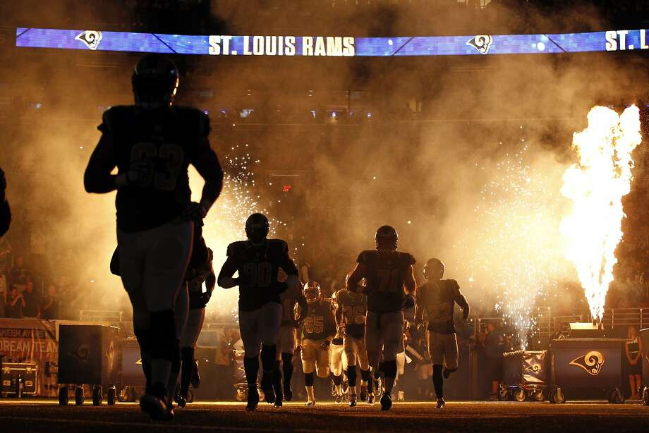 Members of the St. Louis Rams run on the field before an NFL football game against the Pittsburgh Steelers, Sunday, Sept. 27, 2015, in St. Louis. The game was delayed because part of the pyrotechnics used during the introductions briefly caught the turf on fire. (AP Photo/Billy Hurst) Photo: Billy Hurst, Associated Press