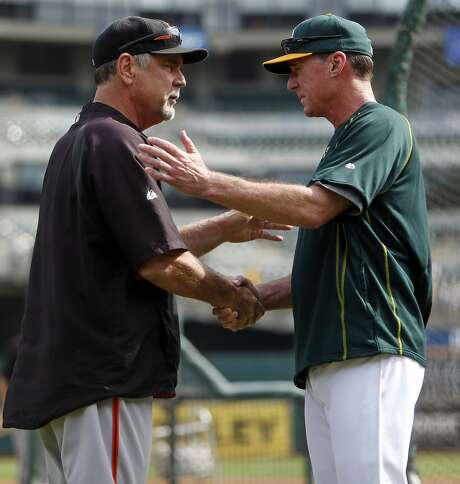 San Francisco Giants' manager Bruce Bochy greets Oakland A's manager Bob Melvin before MLB game at O.co Coliseum in Oakland, Calif., on Sunday, September 27, 2015. Photo: Scott Strazzante, The Chronicle