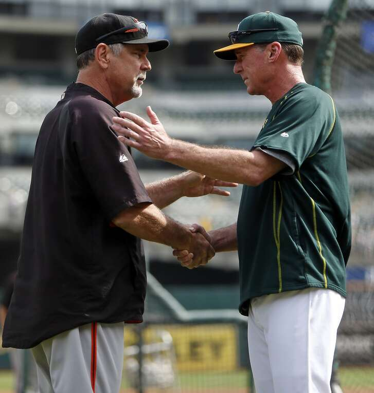 San Francisco Giants' manager Bruce Bochy greets Oakland A's manager Bob Melvin before MLB game at O.co Coliseum in Oakland, Calif., on Sunday, September 27, 2015.