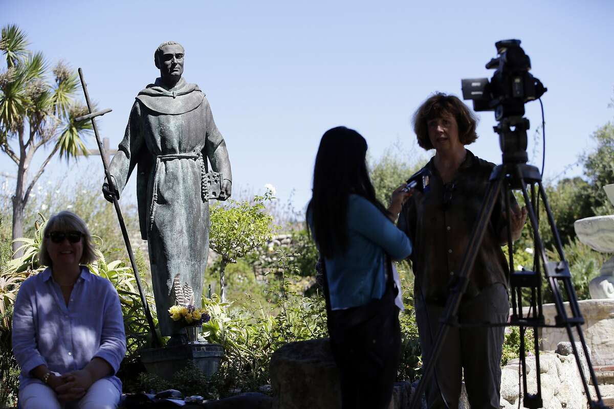 An interview is conducted next to a statue of Junipero Serra at the Carmel Mission, Wednesday, Sept. 23, 2015, in Carmel-By-The-Sea, Calif. Serra, an 18th-century missionary who brought Catholicism to the American West Coast, was elevated to sainthood Wednesday by Pope Francis in the first canonization on U.S. soil.