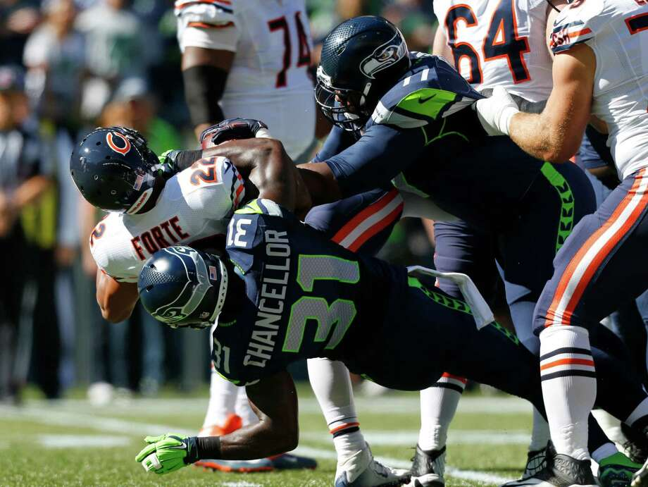 Seattle Seahawks' strong safety Kam Chancellor (31) and defensive tackle Ahtyba Rubin right, tackle Chicago Bears running back Matt Forte, upper left, in the first half of an NFL football game, Sunday, Sept. 27, 2015, in Seattle. (AP Photo/John Froschauer) Photo: John Froschauer, Associated Press / FR74207 AP