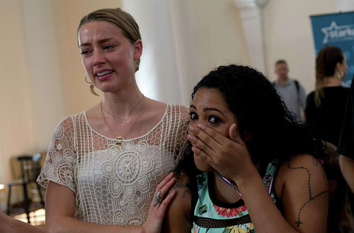 American actress Amber Heard, left, cries with Daniele Lopes, 32, after Daniele received a hearing device in Rio de Janeiro, Brazil, Thursday, Sept. 24, 2015. Starkey Hearing Foundation and the Hollywood Vampires band are joining forces in Rio de Janeiro to provide more than 200 children and adults in need the gift of hearing in advance of the supergroup's performance on the main stage at the Brazilian edition of Rock in Rio festival.