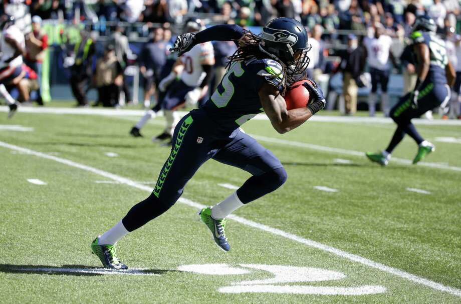Seattle Seahawks cornerback Richard Sherman takes off on a 64-yard punt-return run against the Chicago Bears in the first half of an NFL football game, Sunday, Sept. 27, 2015, in Seattle. (AP Photo/Elaine Thompson) Photo: Elaine Thompson, Associated Press / AP