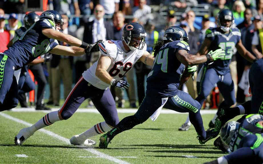 Seattle Seahawks running back Marshawn Lynch (24) runs the ball as Chicago Bears outside linebacker Jared Allen (69) reaches for a tackle attempt while being blocked by Seahawks' tight end Cooper Helfet, left, in the first half of an NFL football game, Sunday, Sept. 27, 2015, in Seattle. (AP Photo/Elaine Thompson) Photo: Elaine Thompson, Associated Press / AP