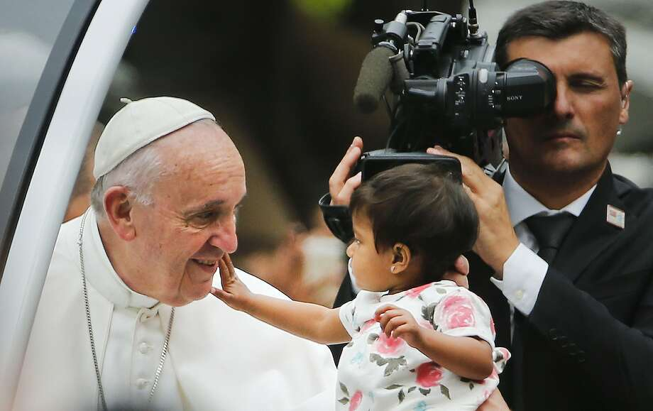 An unidentified child, who was carried out from the crowd to meet Pope Francis, reaches out to touch the Pontiff's face during a parade on his way to celebrate Sunday Mass on the Benjamin Franklin Parkway in Philadelphia, Sunday, Sept. 27, 2015. Pope Francis is in Philadelphia for the last leg of his six-day visit to the United States. (AP Photo/Pablo Martinez Monsivais) Photo: Pablo Martinez Monsivais, Associated Press