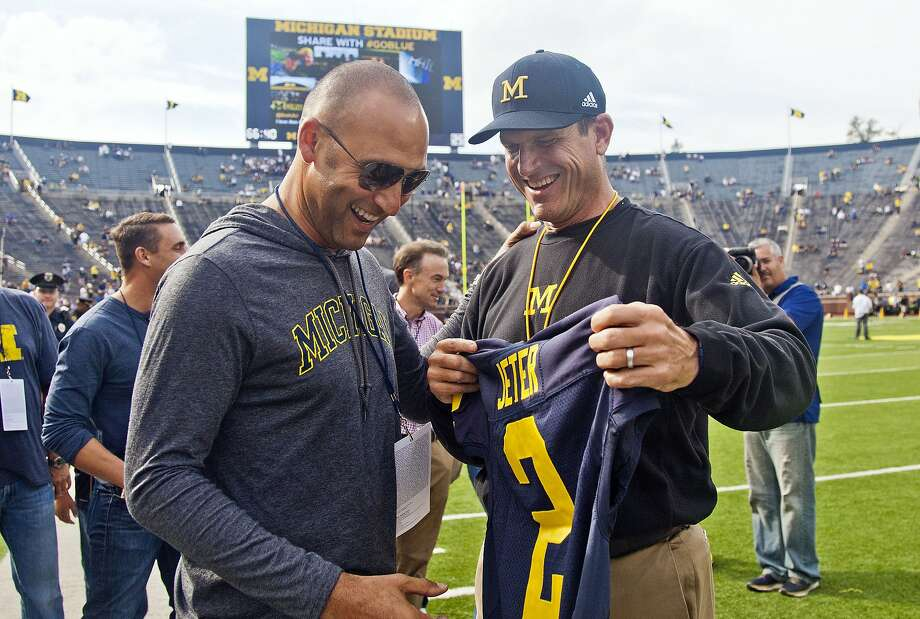 Former Yankees shortstop Derek Jeter (left), who grew up in Kalamazoo, receives a Michigan jersey from head coach Jim Harbaugh before the Wolverines' 31-0 win over BYU in Ann Arbor. Photo: Tony Ding, Associated Press