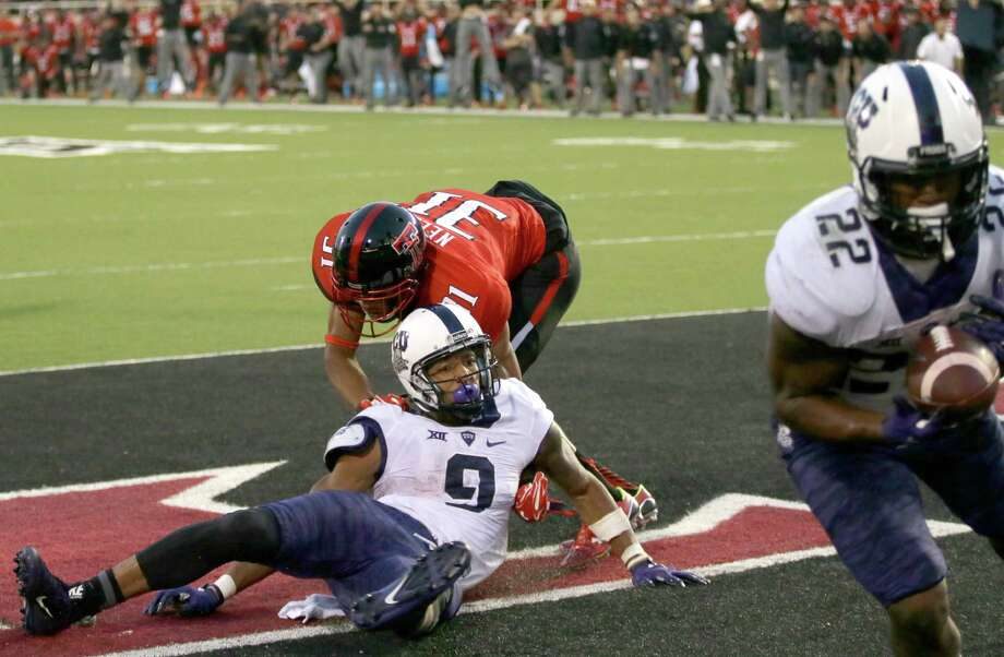 Texas Tech defensive back Justis Nelson (31) grabs TCU wide receiver Josh Doctson (9) after a pass was deflected to running back Aaron Green (22) for a touchdown during the fourth quarter on Sept. 26, 2015, in Lubbock, Texas. Photo: LM Otero /Associated Press / AP