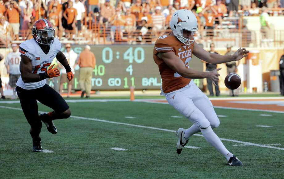 Texas' Michael Dickson (13) bobbles the snap on a punt-attempt as Oklahoma State's Chris Lacy (15) pressures him during the second half of an NCAA college football game, Saturday, Sept. 26, 2015, in Austin, Texas. Oklahoma State won 30-27. (AP Photo/Eric Gay) Photo: Eric Gay, STF / Associated Press / AP