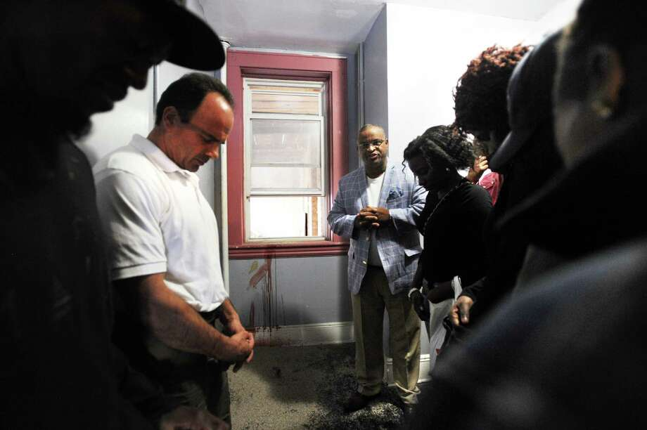 Bridgeport Democratic mayoral candidate Joe Ganim, left and Rev. Harris Howell join with family members for a prayer at the site of the murder of Duhaney Watson in the a stairwell at 159 Charles Street in Bridgeport, Conn. on Sunday, September 27, 2015. Watson's blood can be seen streaked on the wall. Photo: Brian A. Pounds / Hearst Connecticut Media / Connecticut Post