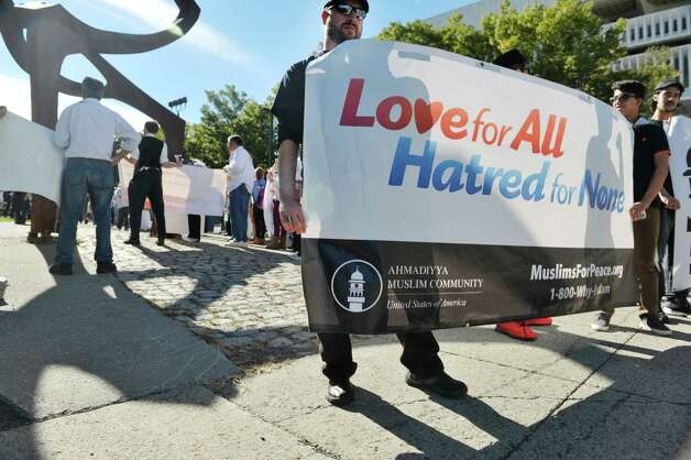 Ahmadiyya Muslim Community members, Noah Ahmad Quick, left, and Haroon Muhammad hold a sign for their community during the North Star Peace Walk on Sunday, September 27, 2015, in Albany, N.Y.  The interfaith 1.5 mile walk took participants to various churches and war memorials, where speakers at each site spoke about peace in the world.    (Paul Buckowski / Times Union) Photo: PAUL BUCKOWSKI / 00033440A