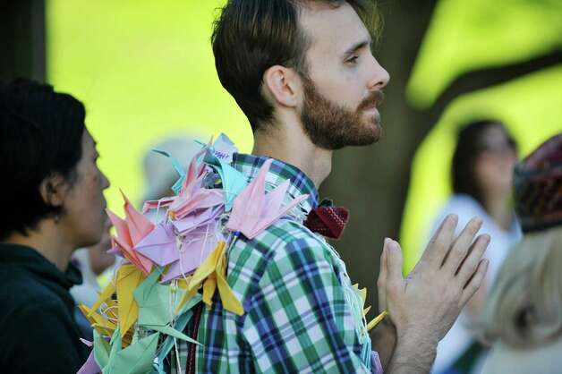 Wearing a chain of peace cranes around his neck, Derek Healey, president of the UAlbany Interfaith Coalition, listens to a speaker during the North Star Peace Walk on Sunday, September 27, 2015, in Albany, N.Y.  The interfaith 1.5 mile walk took participants to various churches and war memorials, where speakers at each site spoke about peace in the world.    (Paul Buckowski / Times Union) Photo: PAUL BUCKOWSKI / 00033440A