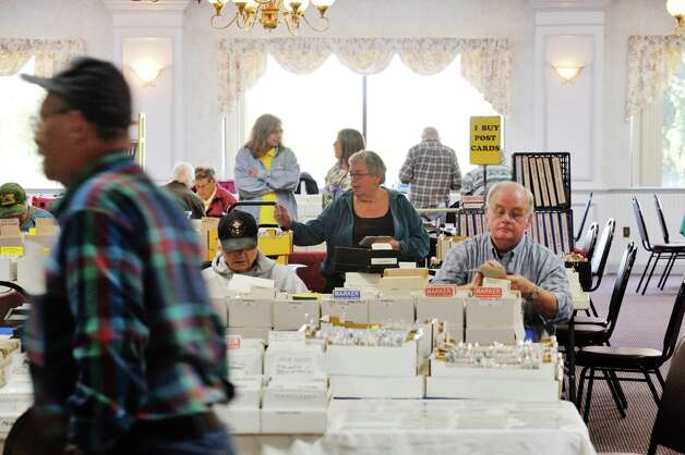 "Post card collectors search through the boxes of cards at the 42nd Annual Upstate New York Post Card Club Show at the Elks Lodge #141 on Sunday, September 27, 2015, in Troy, N.Y.  The yearly event began in the 1970's in Amsterdam.  Today the club has 50 active members and Jim Smoak, club secretary, siad that the show is a way for the club to promote the hobby.  ""The great thing about post card collecting is that there are no bounds.  You buy one post card and then you start looking closer and you see things in the image and that leads you to investigate more about the scene.  You start to ask questions"", Smoak said.  (Paul Buckowski / Times Union) Photo: PAUL BUCKOWSKI / 00033439A"