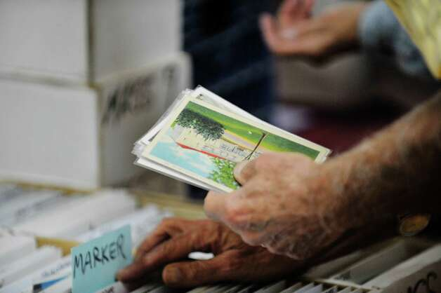 "A post card collector searches through a box of cards at the 42nd Annual Upstate New York Post Card Club Show at the Elks Lodge #141 on Sunday, September 27, 2015, in Troy, N.Y.  The yearly event began in the 1970's in Amsterdam.  Today the club has 50 active members and Jim Smoak, club secretary, siad that the show is a way for the club to promote the hobby.  ""The great thing about post card collecting is that there are no bounds.  You buy one post card and then you start looking closer and you see things in the image and that leads you to investigate more about the scene.  You start to ask questions"", Smoak said.  (Paul Buckowski / Times Union) Photo: PAUL BUCKOWSKI / 00033439A"