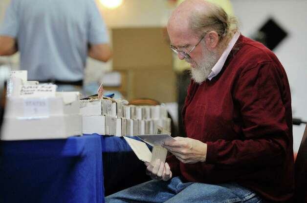 "Post card collector Todd Weseloh of Syracuse looks through cards at the 42nd Annual Upstate New York Post Card Club Show at the Elks Lodge #141 on Sunday, September 27, 2015, in Troy, N.Y.  Weseloh started collecting post cards in the early 1970's and even worked as a dealer of post cards for several years.  The yearly event began in the 1970's in Amsterdam.  Today the club has 50 active members and Jim Smoak, club secretary, said that the show is a way for the club to promote the hobby.  ""The great thing about post card collecting is that there are no bounds.  You buy one post card and then you start looking closer and you see things in the image and that leads you to investigate more about the scene.  You start to ask questions"", Smoak said.  (Paul Buckowski / Times Union) Photo: PAUL BUCKOWSKI / 00033439A"