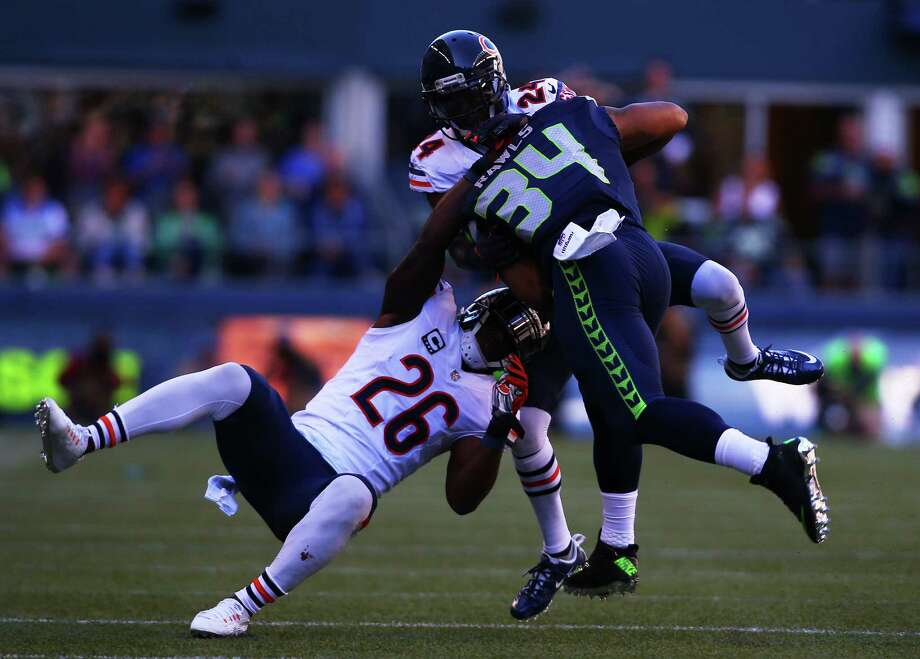 Seattle's Thomas Rawls (34) is taken down by Chicago's Antrel Rolle (26) and Alan Ball (24) after picking up 21 yards on a run in the third quarter of the Seahawks home opening game against Chicago at CenturyLink Field, Sunday, September 27, 2015. The Seahawks won 26-0. Photo: GENNA MARTIN, SEATTLEPI.COM / SEATTLEPI.COM