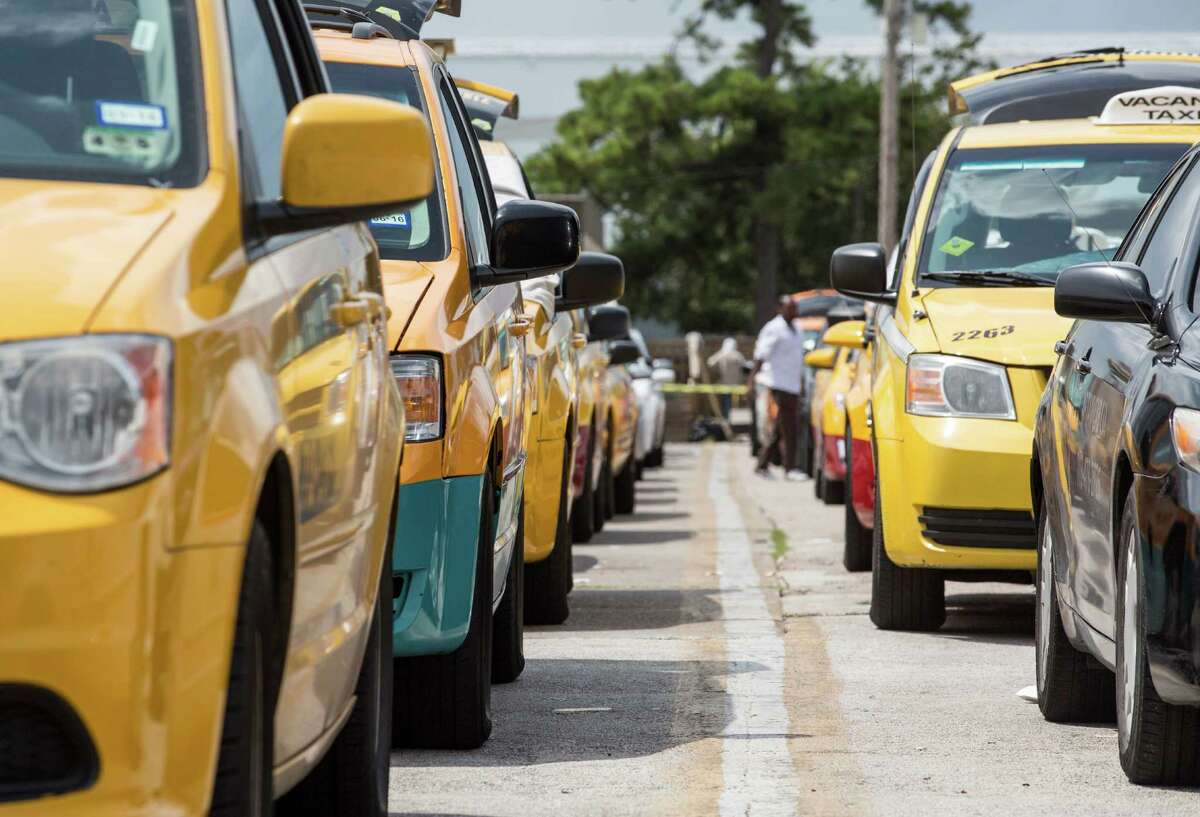 """Taxis line up in an area known as the """"queue"""" as they wait for their turn to wait for passengers at George Bush Intercontinental Airport."""