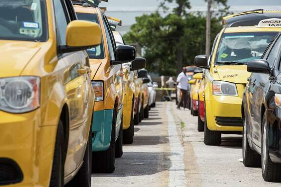 "Taxis line up in an area known as the ""queue"" as they wait for their turn to wait for passengers at George Bush Intercontinental Airport."