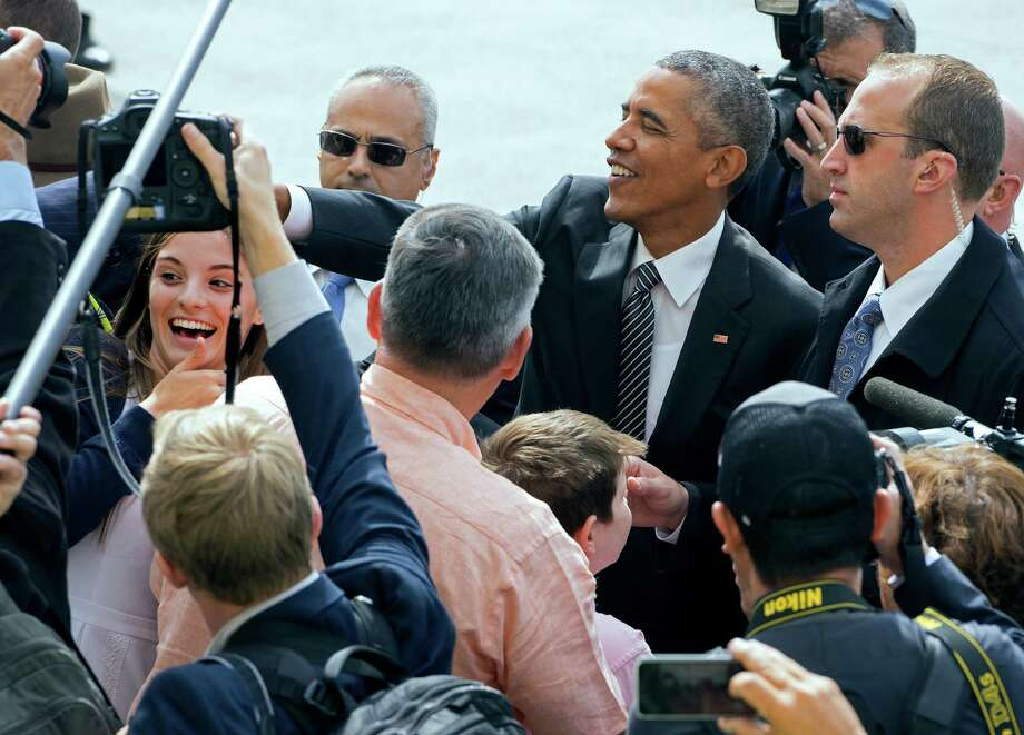 President Barack Obama greets guests after arriving at John F. Kennedy International Airport in New York, Sunday, Sept. 27, 2015. Obama and the leaders of some of America's most stalwart allies will address the 2015 Sustainable Development Summit on its last day Sunday at United Nations headquarters. (AP Photo/Craig Ruttle) ORG XMIT: NYCR102 Photo: Craig Ruttle / FR61802 AP