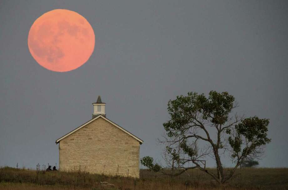 A supermoon rises near Strong City, Kan., Sunday  before a total lunar eclipse. When a full moon makes its closest approach to Earth, it appears bigger and brighter than usual and is known as a supermoon. It was the first time since 1982 that the two events were combined. The next time will be 2033. Photo: Travis Heying, MBO / The Wichita Eagle