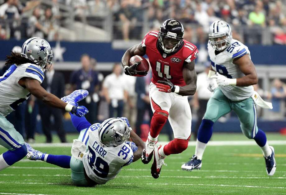 Atlanta Falcons wide receiver Julio Jones (11) breaks a tackle attempt by Dallas Cowboys' Brandon Carr (39) as J.J. Wilcox, left, and Jack Crawford (58) assist on the play in the second half of an NFL football game on Sunday, Sept. 27, 2015, in Arlington, Texas. (AP Photo/Michael Ainsworth) ORG XMIT: CBS169 Photo: Michael Ainsworth / FR171389 AP