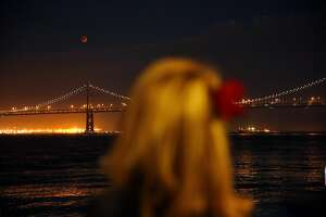 A lunar eclipse appears above the Bay Bridge in San Francisco, Calif., on Sunday, September 27, 2015. Approximately 250-300 people watched the eclipse Sunday evening.
