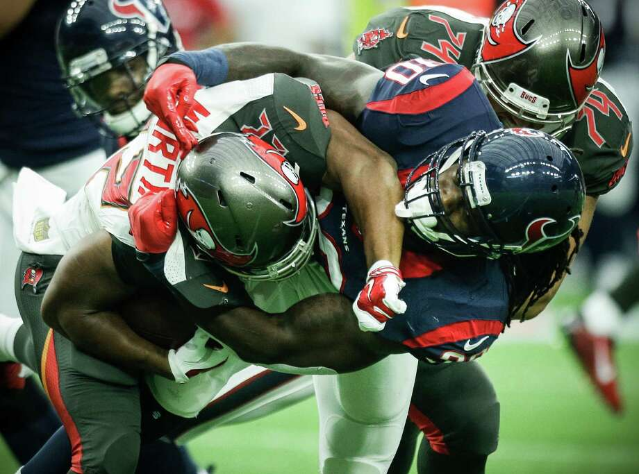 Texans linebacker Jadeveon Clowney, right, stuffs Buccaneers running back Doug Martin at the line of scrimmage during the first quarter Sunday. Clowney had a solo tackle and an assist. Photo: Brett Coomer, Staff / © 2015  Houston Chronicle