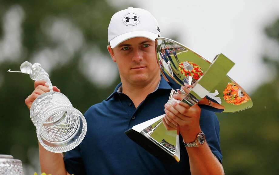 Jordan Spieth looks like he's trying to figure out what to do with the latest additions to his bulging trophy case. Photo: Kevin C. Cox, Staff / 2015 Getty Images