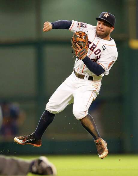 Astros second baseman Jose Altuve goes all out trying to make an off-balance throw to first to nail the Rangers' Mike Napoli in the seventh inning. At the plate, Altuve whacked his 37th double of the season. Photo: Karen Warren, Staff / © 2015 Houston Chronicle