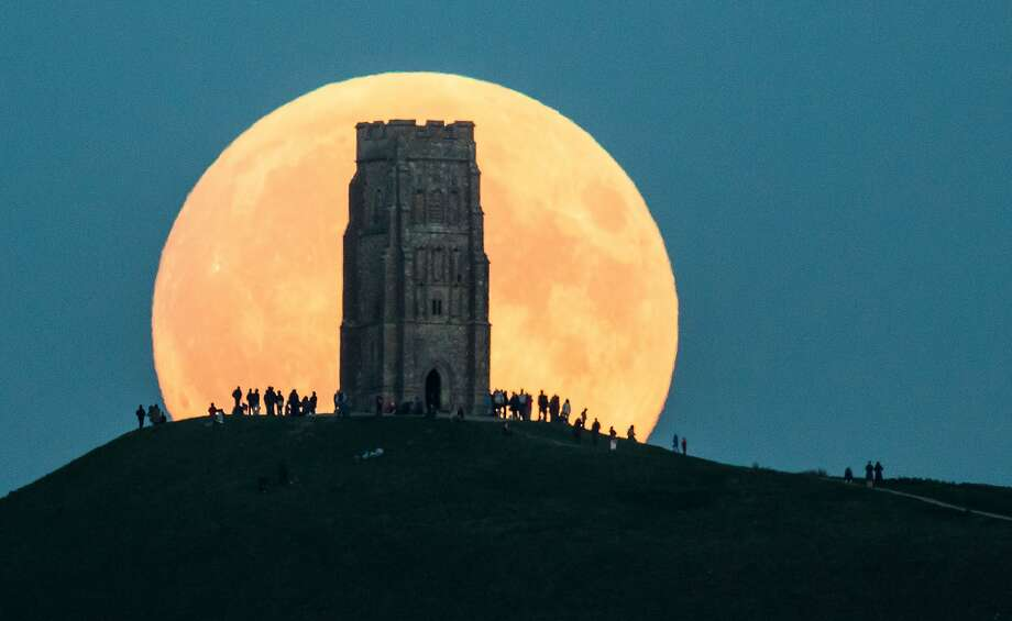 The supermoon rises behind Glastonbury Tor on September 27, 2015 in Glastonbury, England. Tonight's supermoon, so called because it is the closet full moon to the Earth this year, is particularly rare as it coincides with a lunar eclipse, a combination that has not happened since 1982 and won't happen again until 2033.  Photo: Matt Cardy