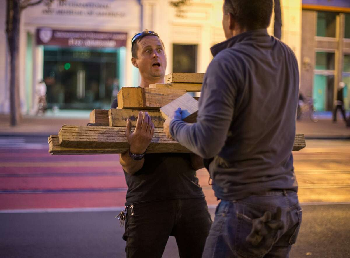 Paul Troutman carries unused wood scraps from the construction of San Francisco's newest Living Innovation Zone designed by artist Marisha Farnsworth and funded by the Kenneth Rainin Foundation, on Market Street between 6th and 7th streets on Sunday, Sept. 27, 2015 in San Francisco, Calif. The installation will open with a ceremony on Wednesday Sept. 30, 2015.