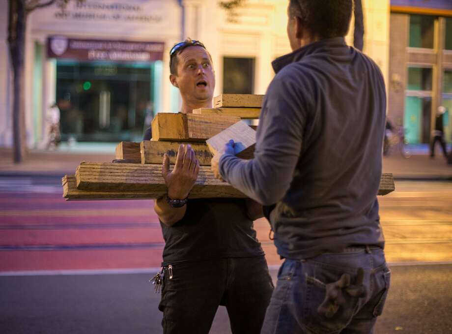 Paul Troutman carries unused wood scraps from the construction of San Francisco's newest Living Innovation Zone. Photo: Nathaniel Y. Downes, The Chronicle