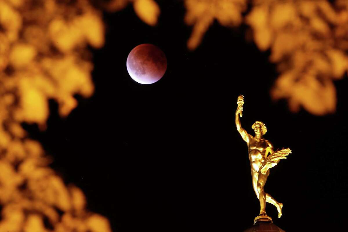 The so-called supermoon appears behind the Golden Boy at the Manitoba Legislature during a lunar eclipse in Winnipeg Manitoba, Sunday, Sept. 27, 2015. (John Woods/The Canadian Press via AP) MANDATORY CREDIT ORG XMIT: JGW105