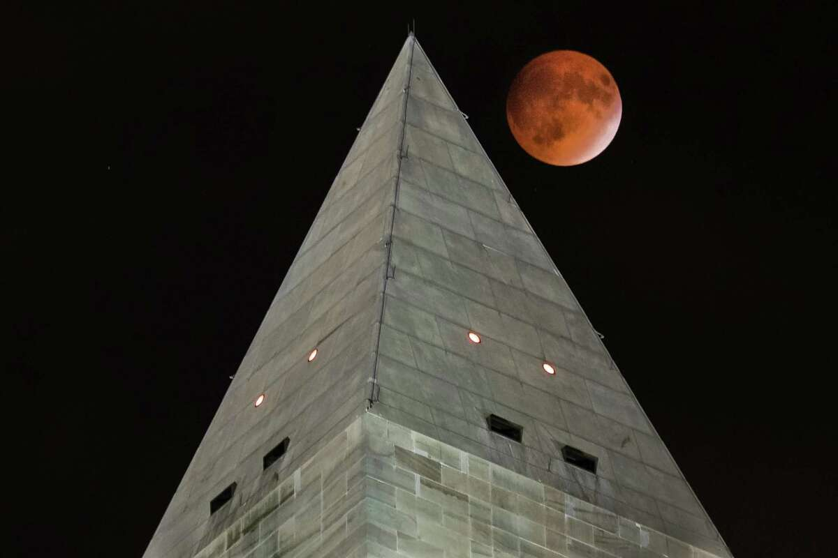 The so-called supermoon passes behind the peak of the Washington Monument during a lunar eclipse, Sunday, Sept. 27, 2015. The supermoon, or perigee moon, occurs when the full or new moon comes closest to the Earth making it appear bigger. t's the first time the events have made a twin appearance since 1982, and they won't again until 2033. (AP Photo/J. David Ake) ORG XMIT: DCDA101