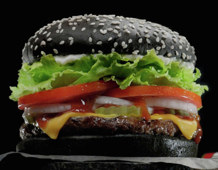 Starting Sept. 28, Burger King is offering a Halloween Whopper made with a black bun in restaurants across the United States. The buns have A.1. steak sauce baked into them to create the pitch black color. Photo: Burger King