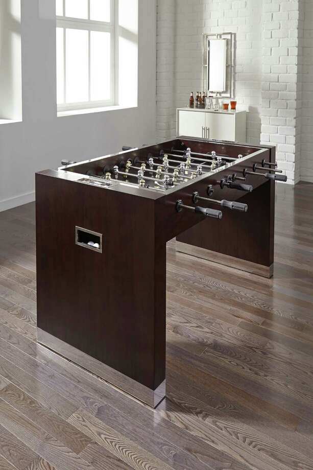The MG&BW Limited Edition foosball table, $4,870, has a walnut veneer and polished stainless-steel detailing.