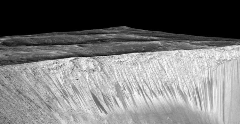 Dark narrow streaks called recurring slope lineae emanating out of the walls of Garni crater on Mars. The dark streaks here are up to few hundred meters in length. They are hypothesized to be formed by flow of briny liquid water on Mars. Photo: NASA/JPL/University Of Arizona