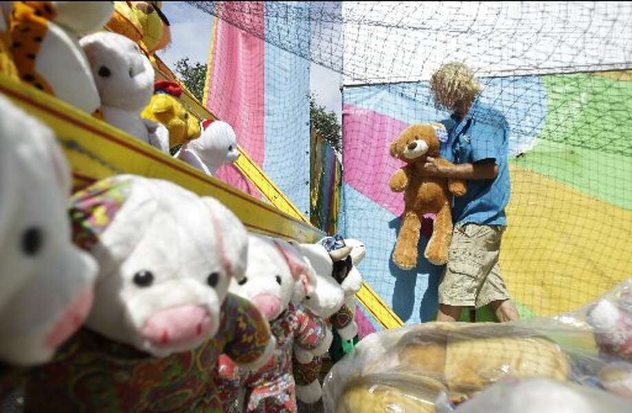Mykel Gibson of Hibbing, MN sets up stuffed animal prizes at a basketball throw game on the carnival midway in 2014. Melissa Phillip / Houston Chronicle.
