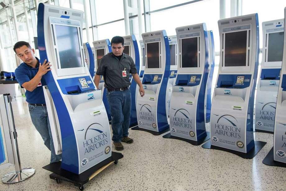 Technicians Linc Mai, left, and Jerry Nguyen wheel a passport kiosk into place at Bush Intercontinental Airport. Photo: Brett Coomer, Staff / © 2015 Houston Chronicle