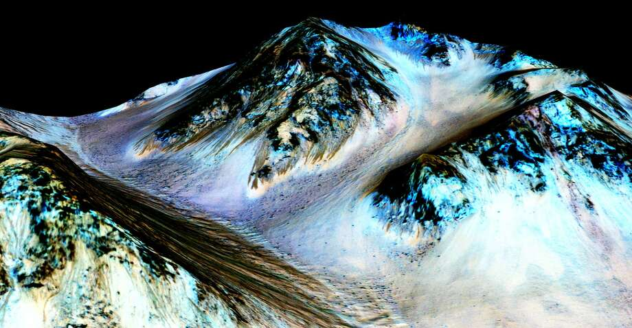 These dark, narrow, 100 meter-long streaks called recurring slope lineae flowing downhill on Mars are inferred to have been formed by contemporary flowing water. Recently, planetary scientists detected hydrated salts on these slopes at Hale crater, corroborating their original hypothesis that the streaks are indeed formed by liquid water. The blue color seen upslope of the dark streaks are thought not to be related to their formation, but instead are from the presence of the mineral pyroxene. The image is produced by draping an orthorectified (Infrared-Red-Blue/Green(IRB)) false color image (ESP_030570_1440) on a Digital Terrain Model (DTM) of the same site produced by High Resolution Imaging Science Experiment (University of Arizona). Vertical exaggeration is 1.5. Photo: NASA/JPL/University Of Arizona