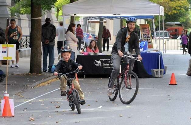 Eric Krans, right, rides a bicycle obstacle course with six-year-old Tate Green as part of the Collar City PreRamble Festival which focused on alternative methods of transportation to cars on Saturday Sept. 26, 2015 in Troy, N.Y.  (Michael P. Farrell/Times Union) Photo: Michael P. Farrell, Albany Times Union / 10033480A