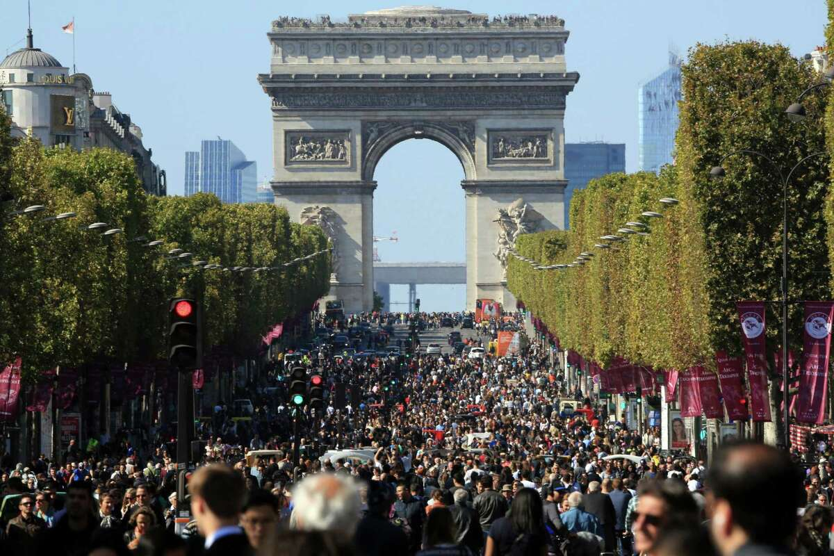 """People walk on the Champs Elysees during the """"day without cars"""", in Paris, France on Sept. 27. Paris Mayor Anne Hidalgo presided over Sunday's """"day without cars,"""" two months before the city hosts the global summit on climate change. (AP Photo/Thibault Camus)"""