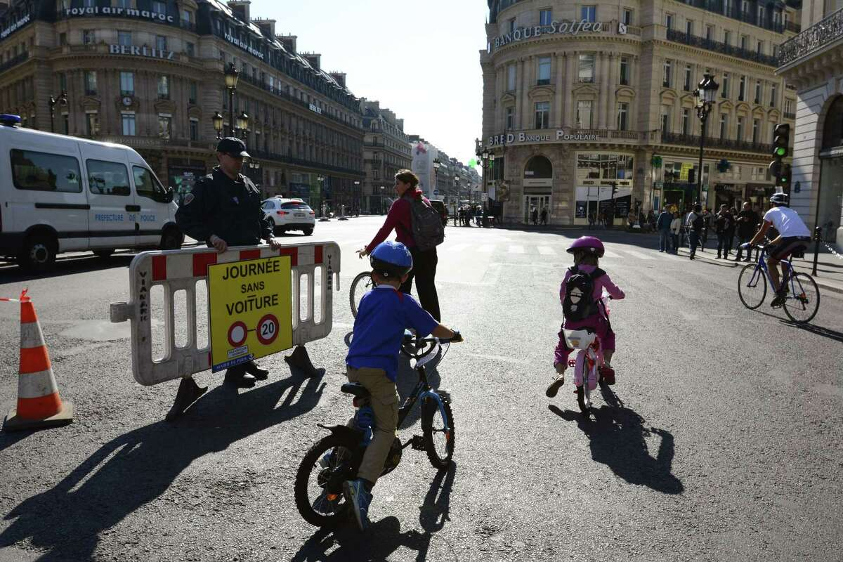 People ride bicycles at Place de l'Opera during the