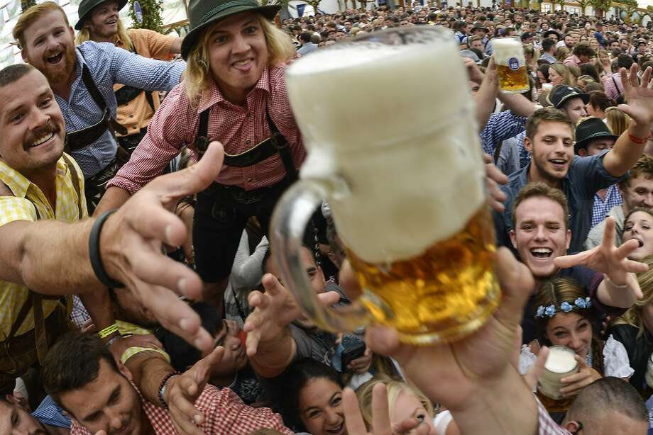 Revelers try to snatch free beer at the hofbräu tent on the opening day of the 2015 Oktoberfest in Munich, Germany.More: Photos of Oktoberfest back in the day Photo: Philipp Guelland, Getty Images