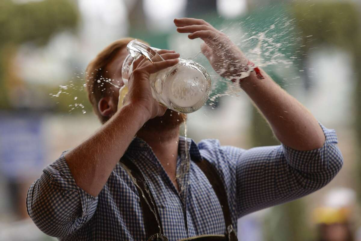 A reveller spills beer as he tries to empty his stein in one sitting at the hofbräu tent on the opening day in Munich, Germany. More: Photos of Oktoberfest back in the day