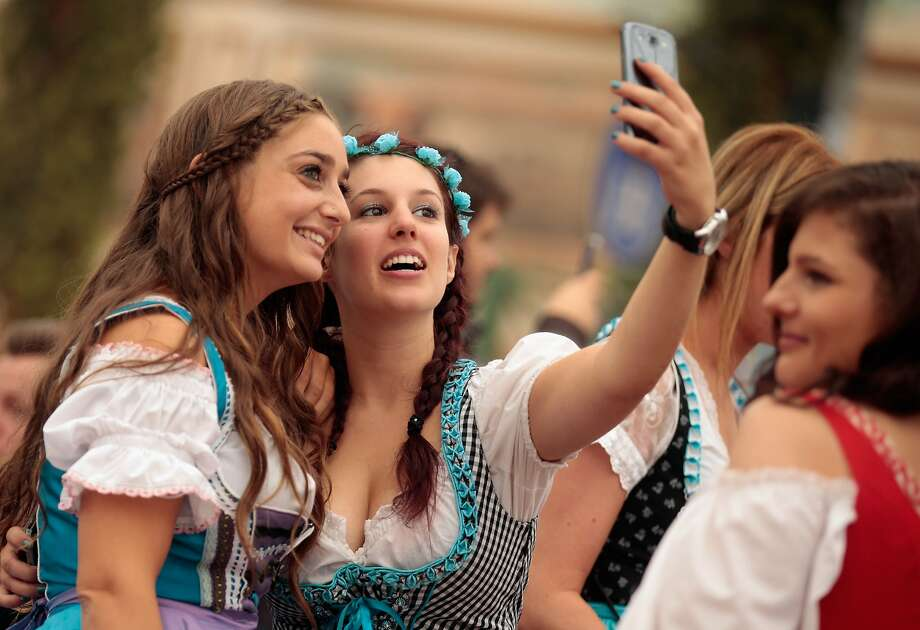 MUNICH, GERMANY - SEPTEMBER 19:  Revelers dressed in Bavarian folk outfits pose for selfies during the opening day of the 2015 Oktoberfest on September 19, 2015 in Munich, Germany. The 182nd Oktoberfest will be open to the public from September 19 through October 4and will draw millions of visitors from across the globe in the world's largest beer fest.  (Photo by Johannes Simon/Getty Images) Photo: Johannes Simon, Getty Images