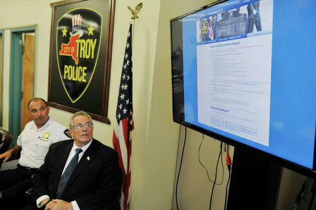 Troy Chief of Police John Tedesco, left, and Troy Mayor Lou Rosamilia look on as a  deomonstration takes place on the monitor for  the new online reporting system, Coplogic, that the police department will be using on Monday, Sept. 28, 2015, in Troy, N.Y.  The system will be available for city residents to use to file reports for non-violent crimes.   (Paul Buckowski / Times Union) Photo: PAUL BUCKOWSKI / 00033522A