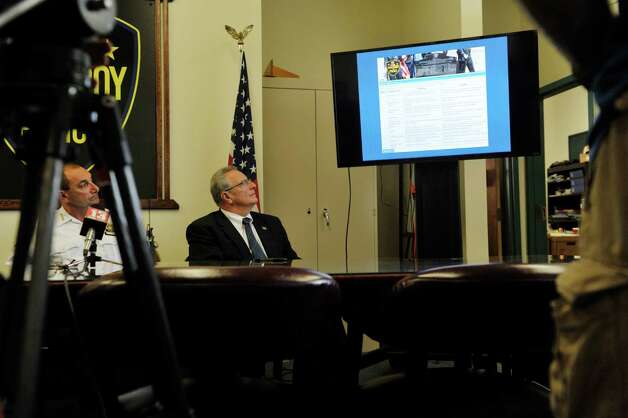 Troy Chief of Police John Tedesco, left, and Troy Mayor Lou Rosamilia look on as a  demonstration takes place on the monitor for  the new online reporting system, Coplogic, that the police department will be using on Monday, Sept. 28, 2015, in Troy, N.Y.  The system will be available for city residents to use to file reports for non-violent crimes.   (Paul Buckowski / Times Union) Photo: PAUL BUCKOWSKI / 00033522A