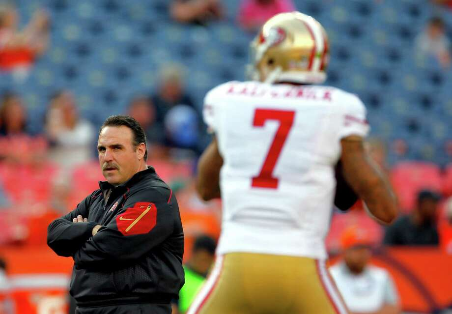 Jim Tomsula watches Colin Kaepernick warm up last month before a preseason game in Denver. Photo: Joe Mahoney / Associated Press / FR170458 AP