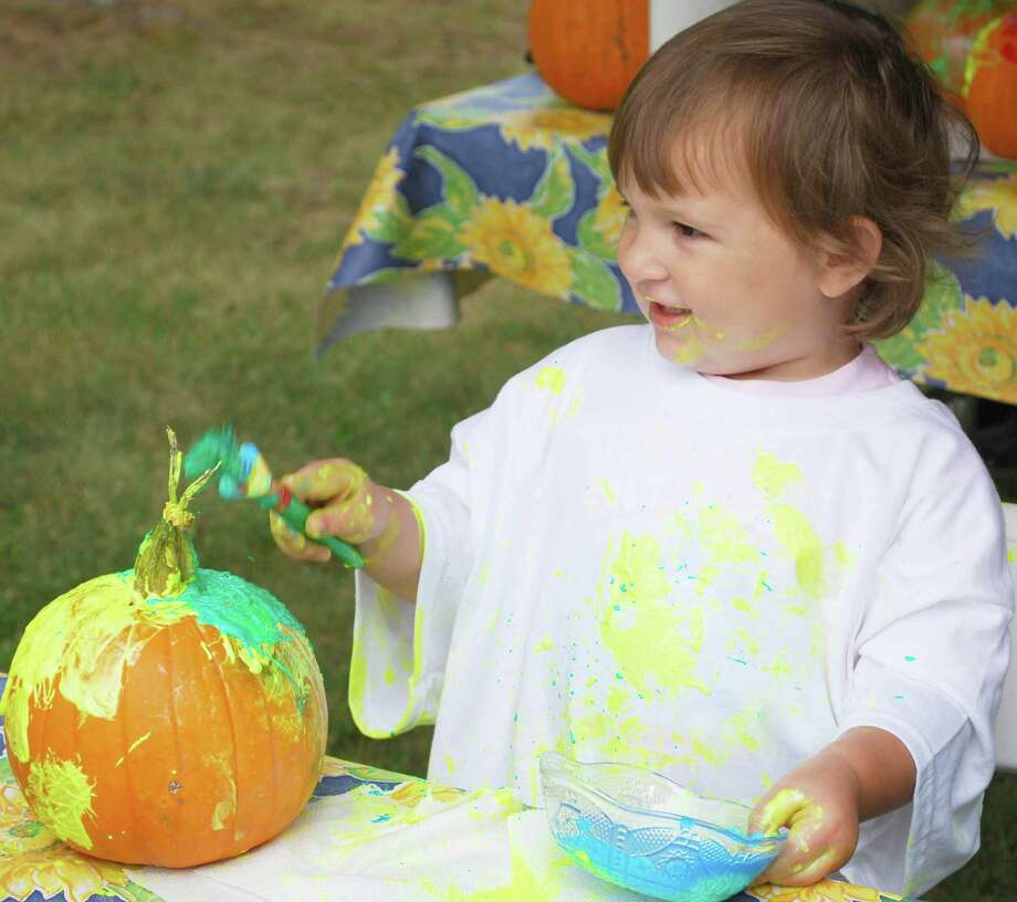 Emily Murphy of Woodbury, who turned 2 on Sept. 24, dabbles in paint as she decorates a pumpkin at Sunny Valley Preserve's 23rd annual Open Farm Day in New Milford Sept. 19, 2015. Photo: Deborah Rose / Deborah Rose / The News-Times